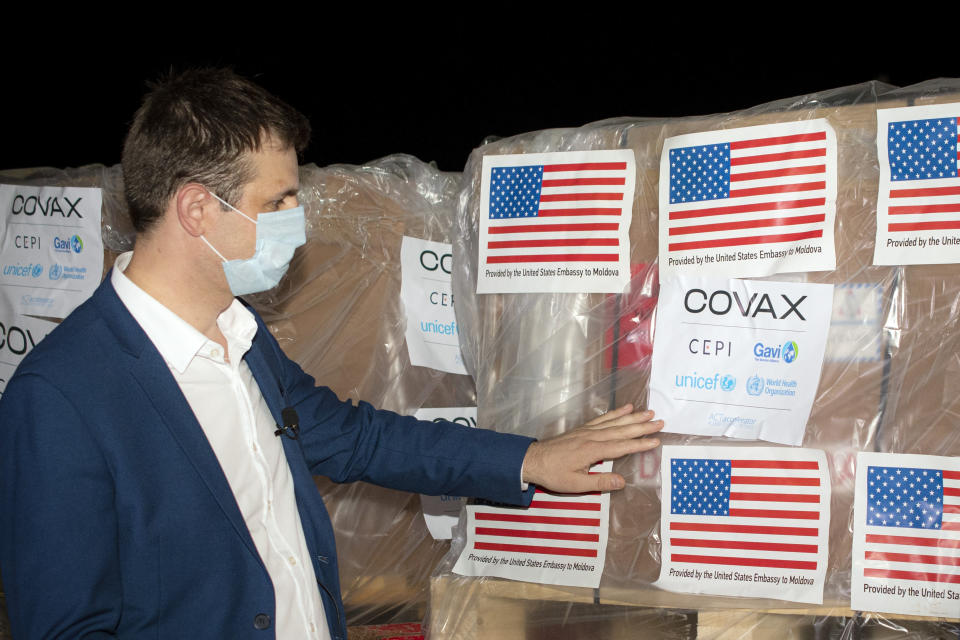 """Veaceslav Gutu from the National Agency for Public Health adjusts a sticker that reads """"Covax"""" on boxes containing COVID-19 vaccines, at the Chisinau International Airport, in Chisinau, Moldova, Monday, July 12, 2021.The first 150,000 doses of a 500,000-strong batch of Johnson & Johnson vaccines arrived in Moldova's capital Monday as part of a donation from the United States that will help the former Soviet republic tackle the coronavirus pandemic.(AP Photo/Nadejda Roscovanu)"""