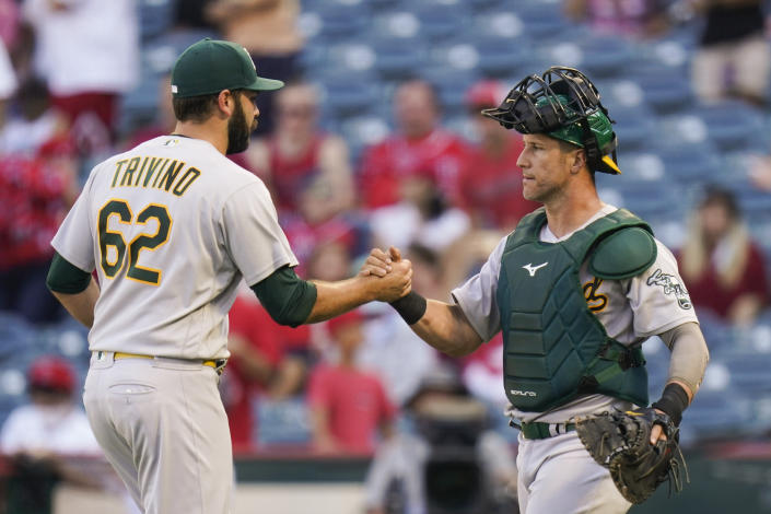 Oakland Athletics relief pitcher Lou Trivino, left, and catcher Yan Gomes celebrate a win in the 10th inning of a baseball game against the Los Angeles Angels, Sunday, Sept. 19, 2021, in Anaheim, Calif. (AP Photo/Jae C. Hong)