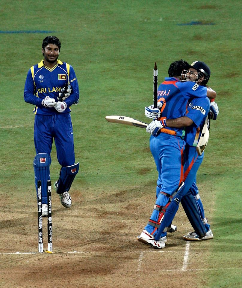 MUMBAI, INDIA - APRIL 02: Yuvraj Singh (C) and M.S.Dhoni of India celebrate watched by Kumar Sangakkara of Sri Lanka after Dhoni hit the winning runs for India to defeat Sri Lanka after India's victory over Sri Lanka in the 2011 ICC World Cup Final between India and Sri Lanka played at Wankhede Stadium on April 2, 2011 in Mumbai, India.  (Photo by Graham Crouch/Getty Images)