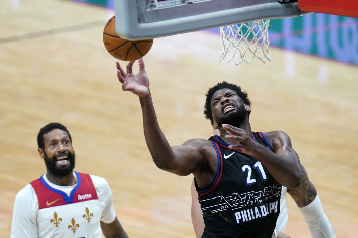 Philadelphia 76ers center Joel Embiid (21) goes to the basket ahead of New Orleans Pelicans forward James Johnson, after center Steven Adams, behind not visible, was called for a foul, which was overturned by a coach's challenge, during the first half of an NBA basketball game in New Orleans, Friday, April 9, 2021. (AP Photo/Gerald Herbert)