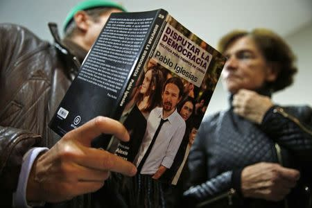 "A man talks about a book he is holding, written by Pablo Iglesias, Secretary General of the party ""Podemos"" (We Can), to a woman at the end of their local assembly in Madrid's Salamanca district December 18, 2014. REUTERS/Susana Vera"