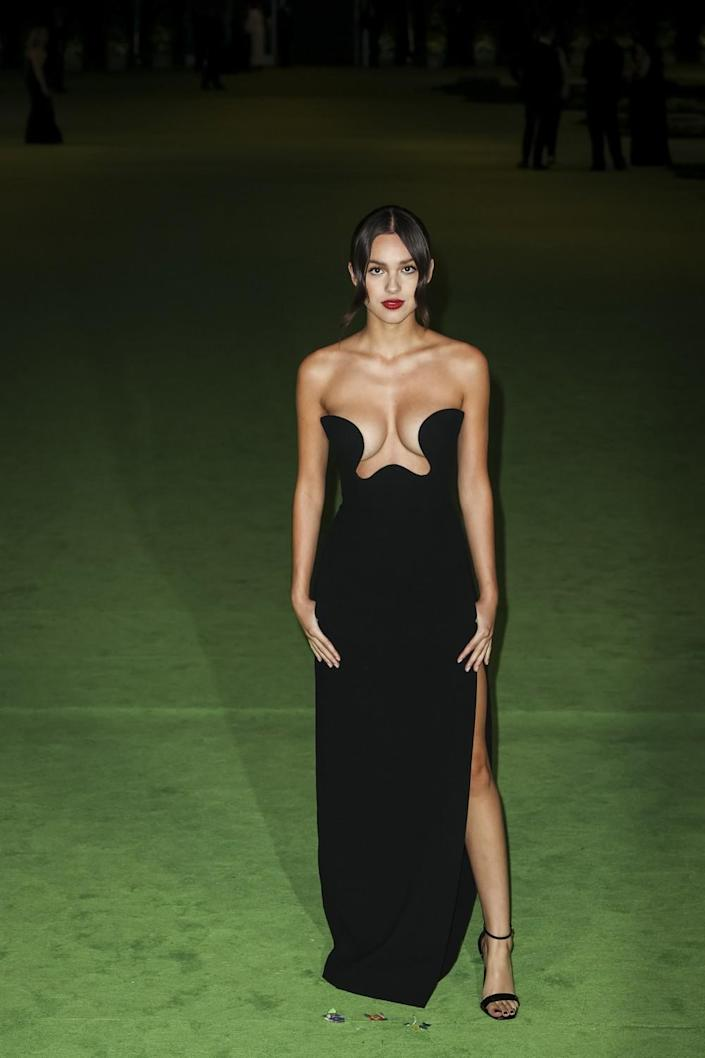 A woman in a black gown posing on a green carpet