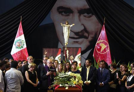 Archbishop Juan Luis Cipriani, Pilar Nores, former wife of Peru's former President Alan Garcia, family members and friends gather around the coffin during a wake, after Garcia fatally shot himself on Wednesday, in Lima, Peru April 18, 2019. REUTERS/Guadalupe Pardo