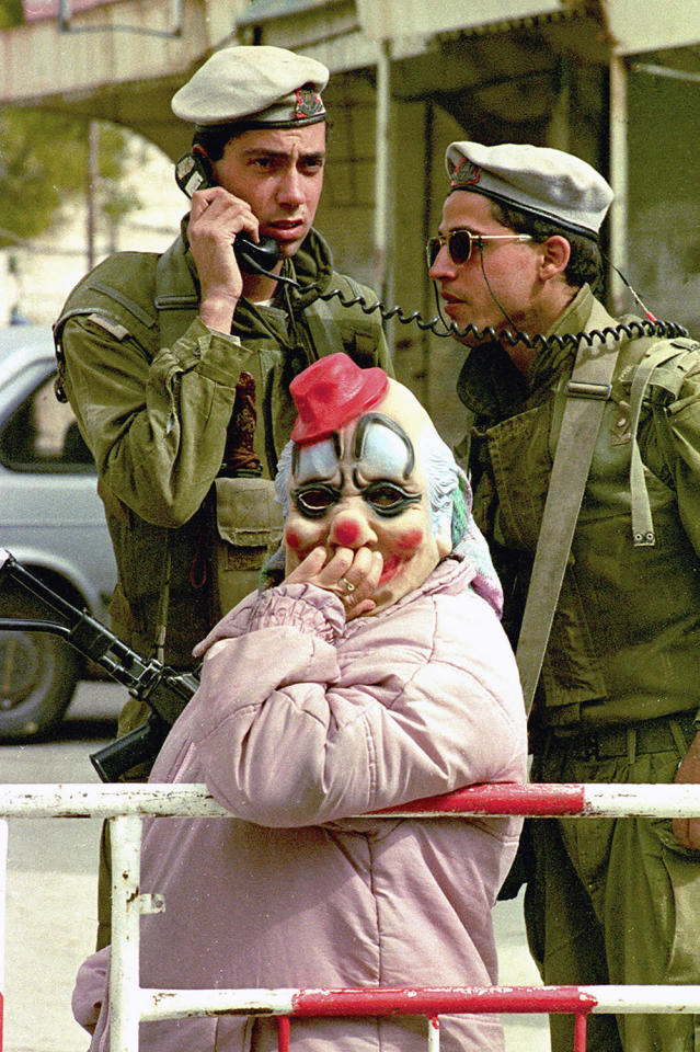 <p>A female Jewish settler dressed as a clown for the Jewish holiday of Purim stands in front of two Israeli soldiers the West Bank town of Hebron, March 7, 1993. (Photo: Jacqueline Larma/AP) </p>