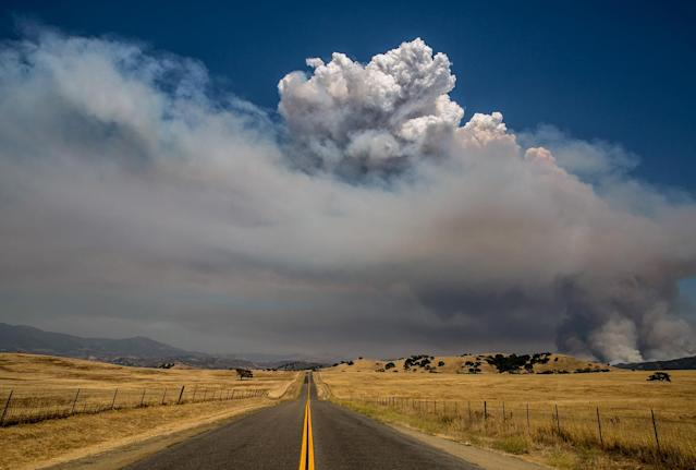<p>Flames and billowing afternoon smoke, caused by the officially named Whittier Fire burning in the coastal mountains, create an eerie scene along Armour Ranch Road on July 8, 2017, near Santa Ynez, California. (George Rose/Getty Images) </p>