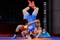 <p>Japan's Shohei Yabiku (blue) wrestles Kazakhstan's Demeu Zhadrayev in their men's greco-roman 77kg wrestling early round match during the Tokyo 2020 Olympic Games at the Makuhari Messe in Tokyo on August 2, 2021. (Photo by Jack GUEZ / AFP)</p>