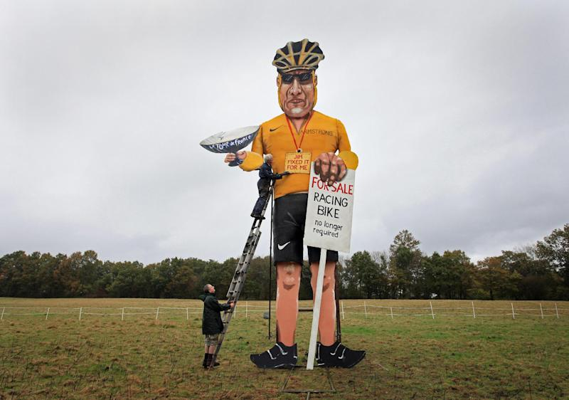 Artist Frank Shepherd, top, poses with his creation of U.S. cyclist Lance Armstrong who has been unveiled as this year's Edenbridge Bonfire Society celebrity guy, during an unveiling for the media in Edenbridge, England, Wednesday Oct. 31, 2012. The Edenbridge Bonfire Society has a long tradition of building symbolic effigies of famous people to burn during their Guy Fawkes bonfire night, and this year it will be disgraced Tour de France cyclist Lance Armstrong who gets torched for his villainy in sport. (AP Photo / Gareth Fuller, PA) UNITED KINGDOM OUT - NO SALES - NO ARCHIVES
