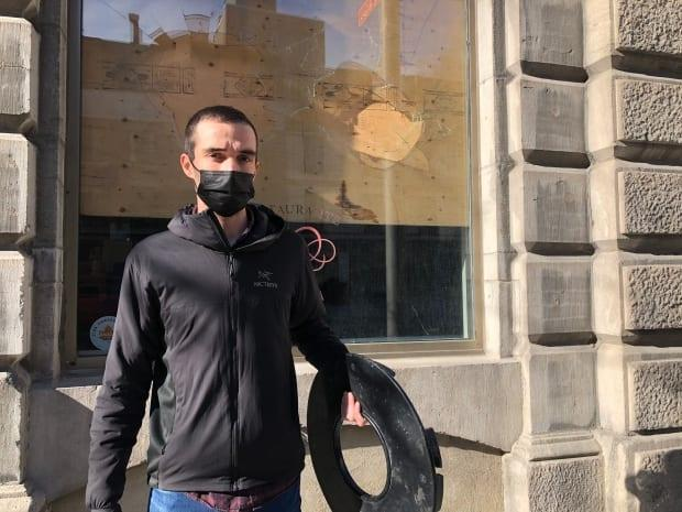 Daniel Loureiro, co-owner of Helena restaurant in Old Montreal, holds a trash can lid that someone tossed through the building's front window on Sunday night.