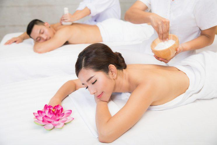 Young couple lying on the massage table and smiling, spa concept. (Photo: Getty Images)