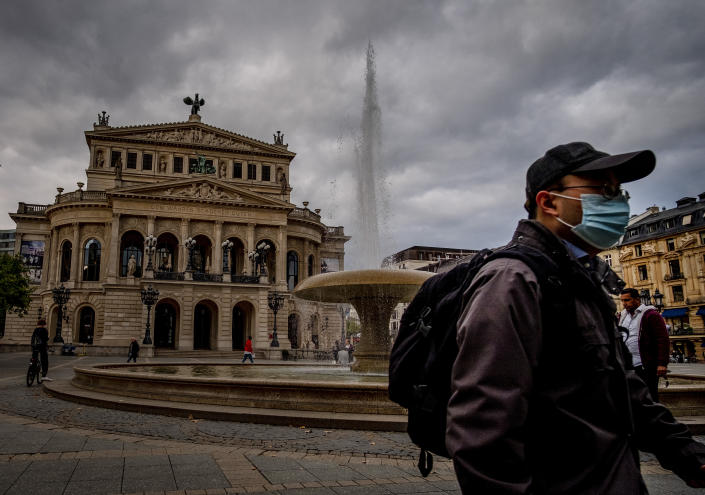 A man wears a face mask as he walks past the Old Opera in Frankfurt, Germany, Monday, Sept. 28, 2020. (AP Photo/Michael Probst)