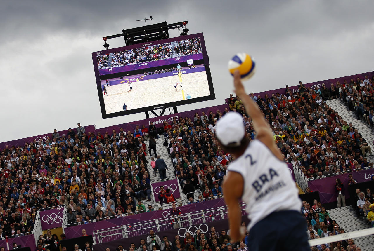 Spectators watch as Brazil's Emanuel serves against Poland's Mariusz Prudel and Grzegorz Fijalek during their men's quarterfinals beach volleyball match at Horse Guards Parade during the London 2012 Olympic Games August 6, 2012.              REUTERS/Marcelo del Pozo (BRITAIN  - Tags: OLYMPICS SPORT VOLLEYBALL)