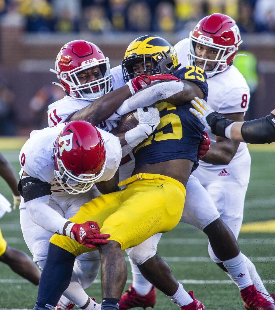 Michigan running back Hassan Haskins (25) is tackled by Rutgers defensive back Christian Izien (0), linebacker Drew Singleton (11), and linebacker Tyshon Fogg (8) in the fourth quarter of an NCAA college football game in Ann Arbor, Mich., Saturday, Sept. 25, 2021. Michigan won 20-13. (AP Photo/Tony Ding)