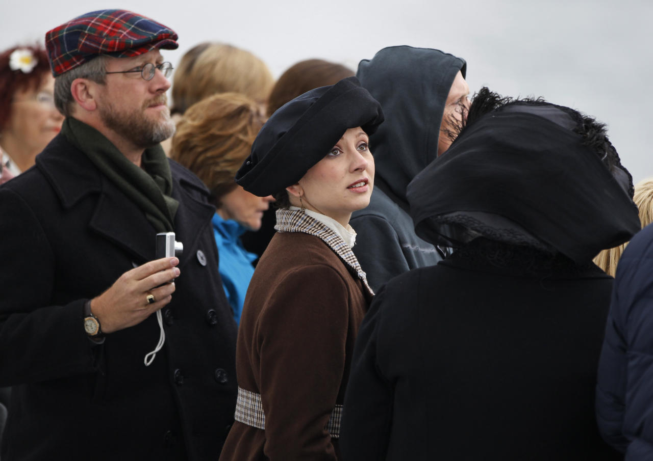 Passengers, including Amy Marie Beechler, center, from Buffalo, NY, in period costume, watch as the MS Balmoral Titanic memorial cruise ship, arrives at New York port, Thursday, April 19, 2012. Exactly 100 years after the Titanic went down, the cruise retraced the ship's voyage, departing from Southampton, England, included a visit Sunday, April 15, to the location where it sank, then a stop in Halifax, Canada and final destination at New York, as of the original intended trip. (AP Photo/Lefteris Pitarakis)