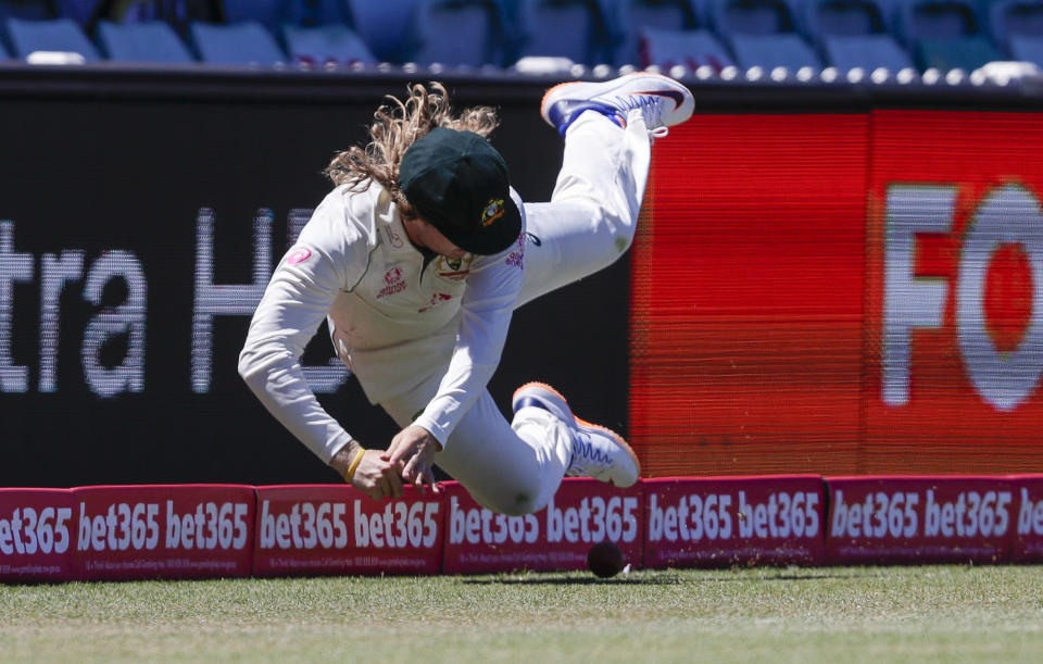 Australia's Will Pucovski is airborne as he fields the ball during play on the final day of the third cricket test between India and Australia at the Sydney Cricket Ground, Sydney, Australia, Monday, Jan. 11, 2021. (AP Photo/Rick Rycroft)