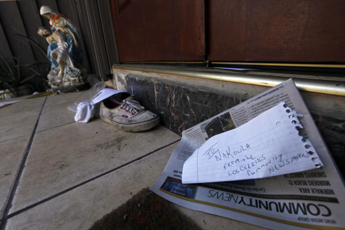 """A religious figure, shoes and a newspaper lie at the steps of the suburban Los Angeles home believed to be that of filmmaker Nakoula Basseley Nakoula, Friday, Sept. 14, 2012. Federal authorities have identified Nakoula, a self-described Coptic Christian, as the key figure behind """"Innocence of Muslims,"""" a film denigrating Islam and the Prophet Muhammad that ignited mob violence against U.S. embassies across the Middle East. (AP Photo/Reed Saxon)"""