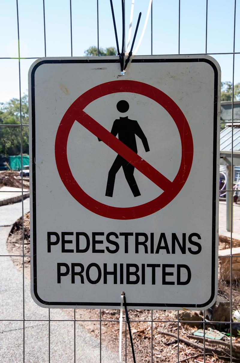 Pictured is a sign on a fence that says pedestrians prohibited.