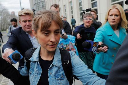 "Actress Allison Mack, known for her role in the TV series ""Smallville"", departs after being granted bail following being charged with sex trafficking and conspiracy in New York"