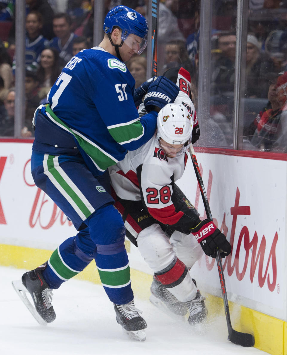 Vancouver Canucks defenceman Tyler Myers (57) puts Ottawa Senators right wing Connor Brown (28) into the boards during the third period of an NHL hockey game Tuesday, Dec. 3, 2019, in Vancouver, British Columbia. (Jonathan Hayward/The Canadian Press via AP)