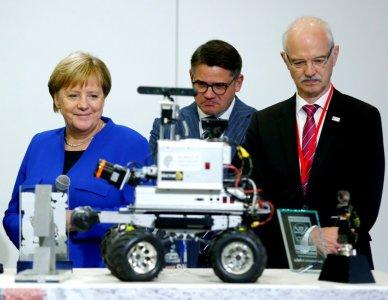 FILE PHOTO: German Chancellor Angela Merkel, Hesse's Science Minister Boris Rhein and President of Darmstadt University of Technology (TU Darmstadt) Hans Jurgen Promel attend a demonstration of a rescue robot at the university in Darmstadt, Germany, October 8, 2018. REUTERS/Ralph Orlowski/File Photo