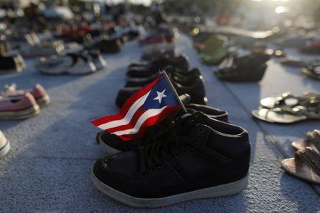 A Puerto Rican flag is seen on a pair of shoes as hundreds of pairs of shoes displayed at the Capitol to pay tribute to Hurricane Maria's victims after a research team led by Harvard University estimated that 4,645 people lost their lives, a number not confirmed by the government, in San Juan, Puerto Rico June 1, 2018. REUTERS/Alvin Baez/Files