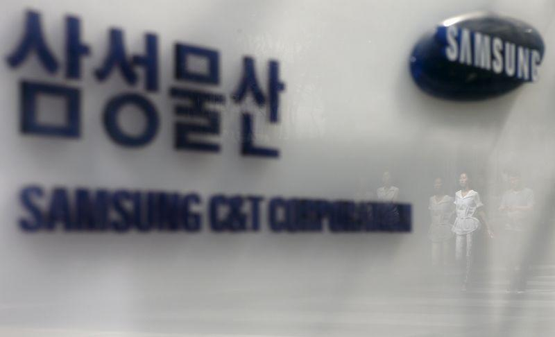 Employees are reflected on a logo of Samsung C&T Corp at the company's headquarters in Seoul