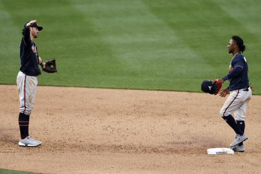 Atlanta Braves' Dansby Swanson, left, and Ozzie Albies celebrate after defeating the New York Mets in a baseball game Saturday, July 25, 2020, in New York. (AP Photo/Adam Hunger)
