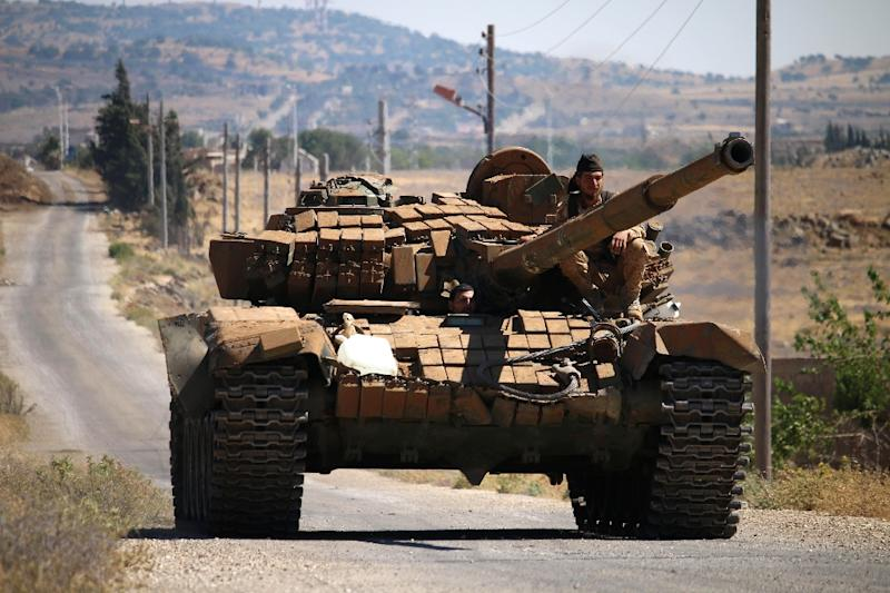 Opposition fighters drive a tank in Syria's southwestern Quneitra province in June 2017 (AFP Photo/Mohamad ABAZEED)