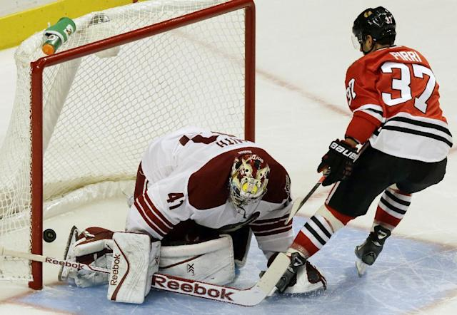 Chicago Blackhawks' Brandon Pirri (37) scores against Phoenix Coyotes goalie Mike Smith in a shootout during an NHL hockey game in Chicago, Thursday, Nov. 14, 2013. The Blackhawks won 5-4. (AP Photo/Nam Y. Huh)