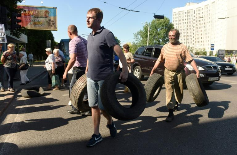 Residents collect tyres to block a road in the western Ukrainian city of Lviv during a protest against the local authorities