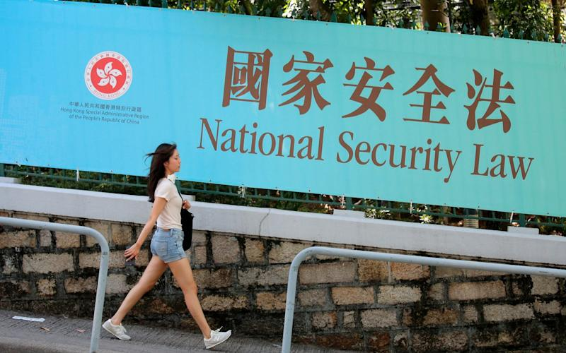 A woman walks past a promotional banner of the national security law for Hong Kong - Kin Cheung/AP