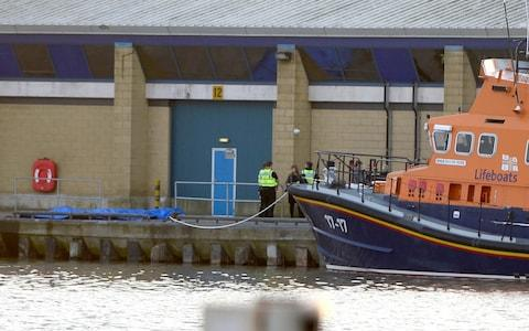 Authorities waiting next to a blue tarpaulin at Grimsby docks - Credit: MEN Media