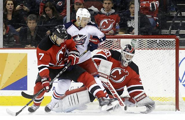 Columbus Blue Jackets right wing Corey Tropp, center, is defended by New Jersey Devils defenseman Mark Fayne, left, and goalie Martin Brodeur during the second period of an NHL hockey game, Friday, Dec. 27, 2013, in Newark, N.J. (AP Photo/Julio Cortez)