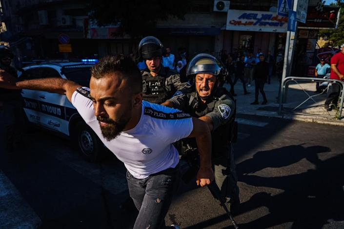 A pedestrian is shoved out of the way as Israeli security forces disperse a crowd.