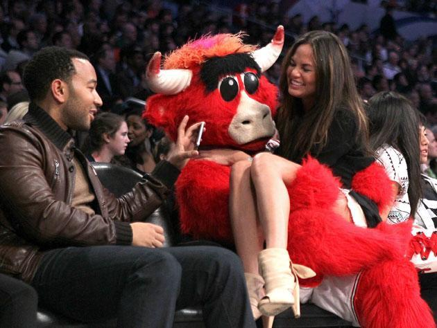 Benny the Bull, the Barry Anderson version, visits with John Legend and Chrissy Teigen. (Getty Images)