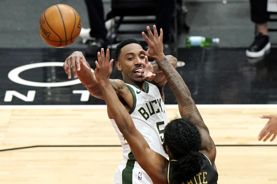 Milwaukee Bucks guard Jeff Teague, top, passes the ball against Chicago Bulls guard Coby White during the first half of an NBA basketball game in Chicago, Friday, April 30, 2021. (AP Photo/Nam Y. Huh)
