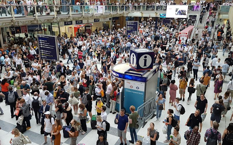 Commuters wait at Liverpool Street station as hot weather continues to cause disruptions and cancellations to trains, after damage to the overhead wires between Luton and London St Pancras International occured yesterday.