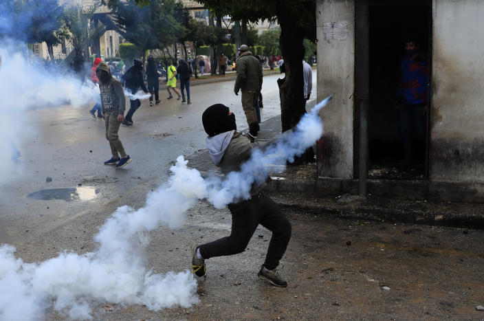 A protester throws back a tear gas canister towards riot policemen during a protest against deteriorating living conditions and strict coronavirus lockdown measures, in Tripoli, north Lebanon, Thursday, Jan. 28, 2021. Violent confrontations between protesters and security forces over the last three days in northern Lebanon left a 30-year-old man dead and more than 220 people injured, the state news agency said Thursday. (AP Photo/Hussein Malla)