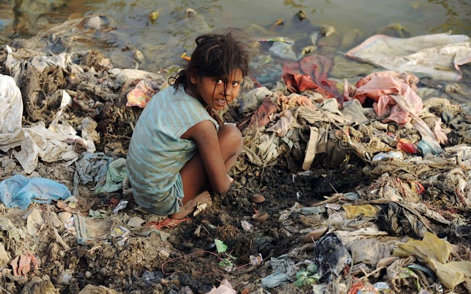 An Indian child searches for coins used in ritual offerings by Hindu devotees on the polluted banks of the river Yamuna in Allahabad - DIPTENDU DUTTA / AFP