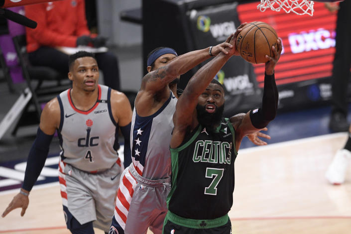 Boston Celtics guard Jaylen Brown (7) goes to the basket against Washington Wizards guard Russell Westbrook (4) and guard Bradley Beal, center, during the first half of an NBA basketball game, Sunday, Feb. 14, 2021, in Washington. (AP Photo/Nick Wass)
