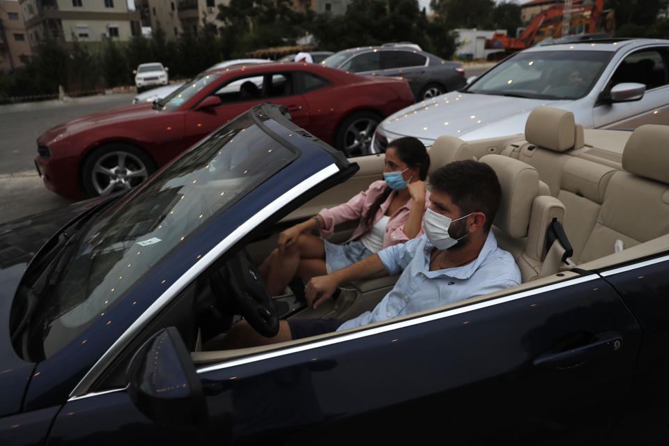 """A couple sit on their car watch """"Hours"""" at a drive-in movie event at a park, in Byblos town, north of Beirut, Lebanon, Friday, July 17, 2020. A group of Lebanese fresh university graduates have launched a drive-in cinema, bringing back the experience that has recently been making a comeback worldwide, as movie theaters remain close because of the coronavirus pandemic. The drive-in cinema experience in Lebanon comes with a special twist, with all proceeds going to needy families to help deal with the country's economic crisis. (AP Photo/Hussein Malla)"""