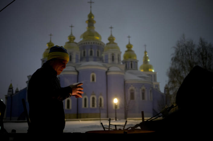 A pro-European Union activist drinks tea to warm himself near a bonfire in St. the Michael's Golden-Domed Monastery in Kiev, Ukraine, Wednesday, Dec. 11, 2013. The Church's Mikhailovsky monastery sheltered and tended to protesters after police swept the square on Sunday, Dec. 1, 2013, causing injuries. (AP Photo/Alexander Zemlianichenko)
