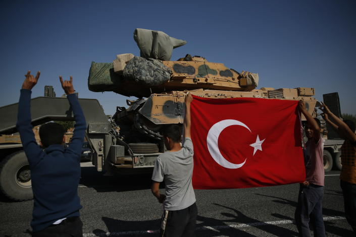 Local residents applaud as a convoy of Turkish forces trucks transporting tanks is driven in Sanliurfa province, southeastern Turkey, at the border with Syria, Saturday, Oct. 12, 2019. Turkey says its military offensive has taken central Ras al-Ayn, a key border town in northeastern Syria, and its most significant gain since its cross-border operation began against Syrian Kurdish fighters began. (AP Photo/Lefteris Pitarakis)