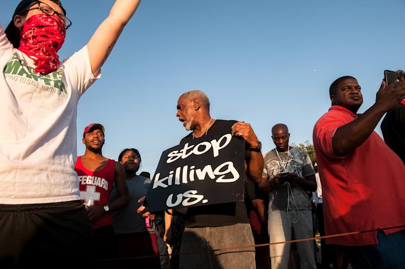 Protesters hold signs as police block their way near the St. Louis Galleria. (Joseph Rushmore for HuffPost)