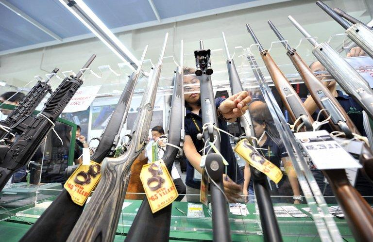 This file photo shows shop employees arranging rifles for sale at a gun show in Manila, on July 15, 2010. There were 1.2 million registered firearms in the Philippines as of last year, according to data from the police firearms and explosives office. There were another roughly 600,000 unlicensed firearms in circulation across the Philippines, according to the office's records