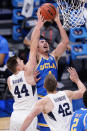 UCLA guard Jaime Jaquez Jr. (4) goes up for a shot as BYU guard Connor Harding (44) and teammate Richard Harward (42) defend during the second half of a first-round game in the NCAA college basketball tournament at Hinkle Fieldhouse in Indianapolis, Saturday, March 20, 2021. (AP Photo/AJ Mast)