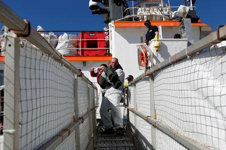A crew member of the Malta-based NGO Migrant Offshore Aid Station (MOAS) ship Phoenix carries a disabled child off the ship after it arrived with migrants and bodies on board, in Augusta on the island of Sicily