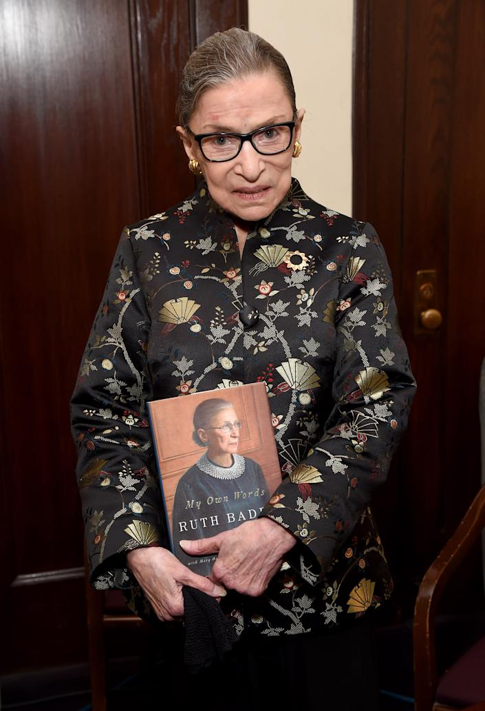 """Ginsburg holds a copy of her book """"My Own Words"""" after an appearance at Temple Emanu-El in New York City. (Photo: Michael Kovac/Getty Images)"""