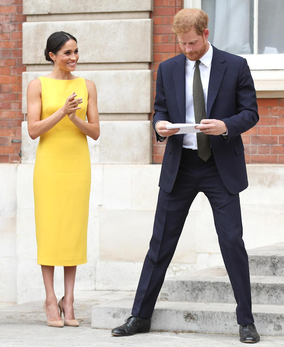 Meghan went sans clutch bag and kept her hands free to applaud her new husband [Photo: Getty]