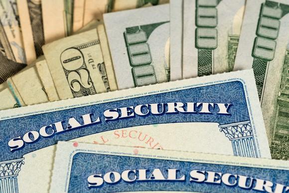 Social Security cards lying atop fanned piles of cash bills.