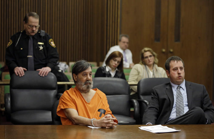 John Donald Cody, center, sits with attorney Joseph Patituce, right, during his sentencing on racketeering, theft, money laundering charges Monday, Dec. 16, 2013, in Cleveland. Cody, using the stolen identity Bobby Thompson, was sentenced to 28 years in prison for defrauding donors of up to $100 million in 41 states through the United States Navy Veterans Association, a charity he ran in Tampa, Fla. (AP Photo/Mark Duncan)